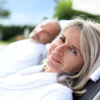 older couple relaxing by the swimming pool