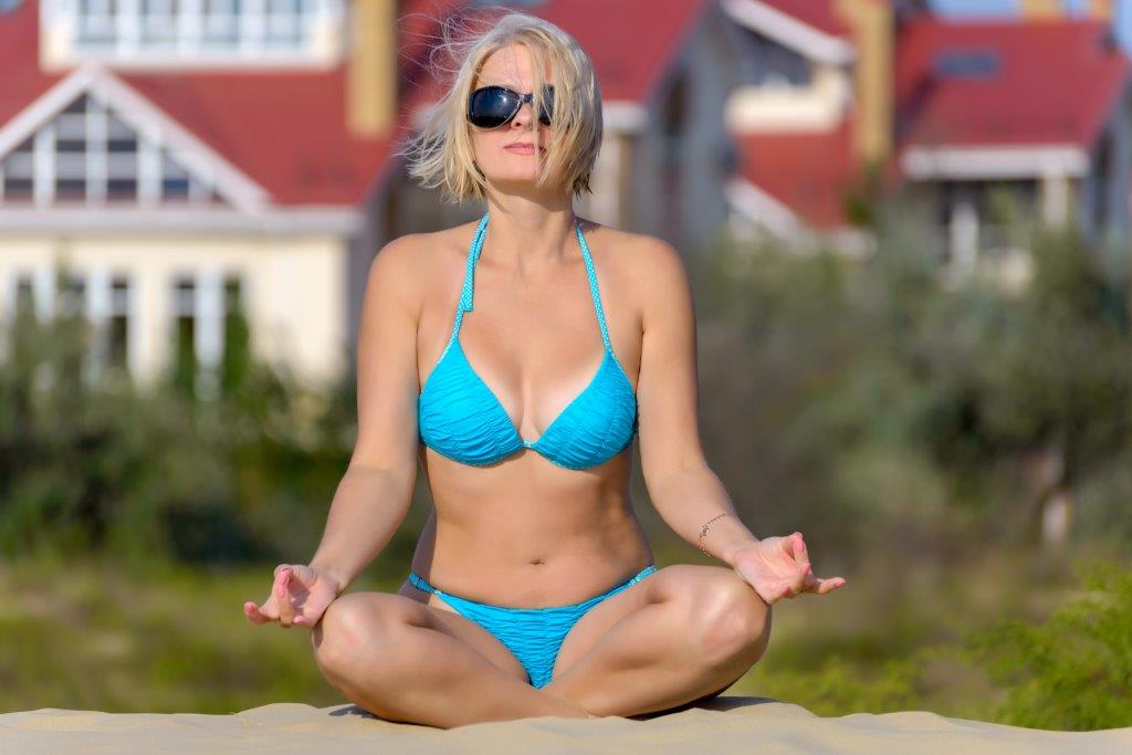 blonde in blue bikini on beach doing yoga