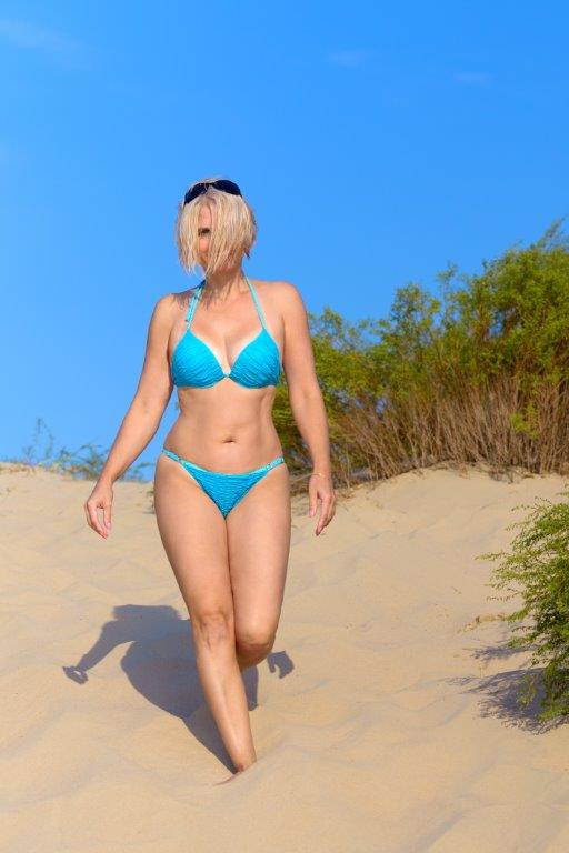 blonde wearing a blue bikini walking on beach