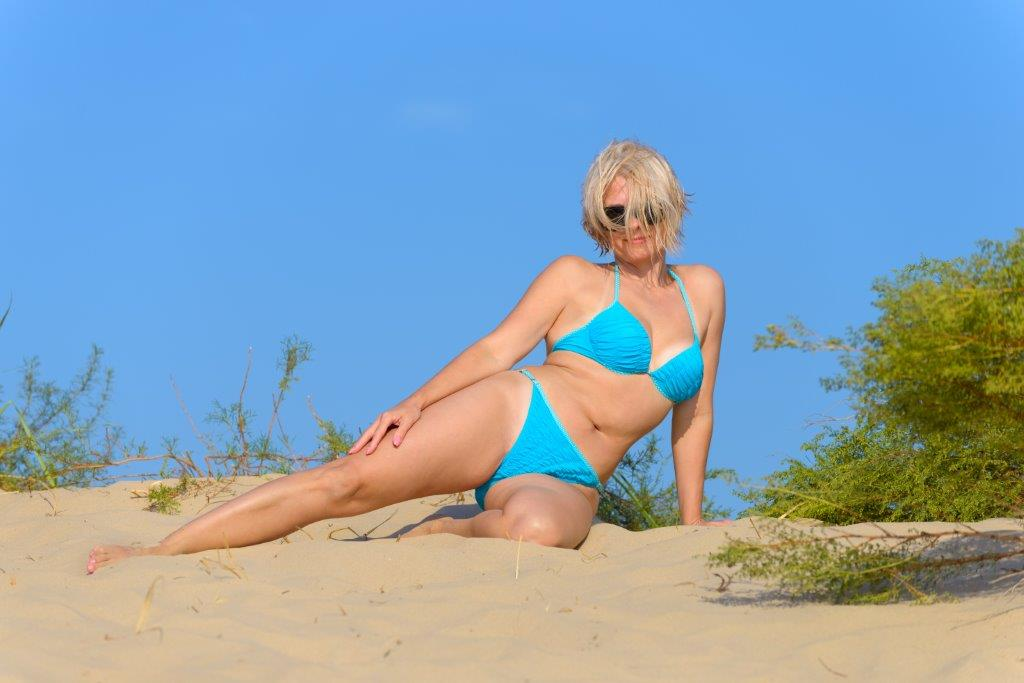 blonde in blue bikini posing in sand