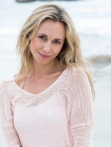 Blonde at beach wearing a pink thin sweater cover-up