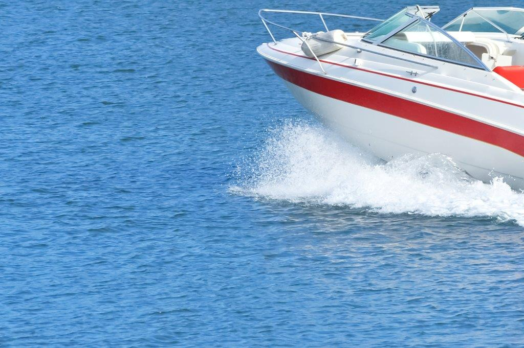 white boat with red stripe going in ocean