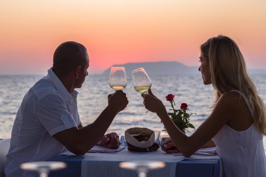 Couple dining on deck of cruise ship at sunset