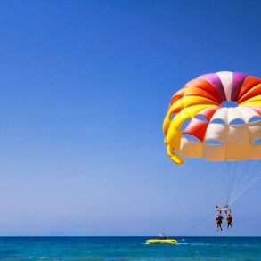 Couple parasailing behind yellow boat