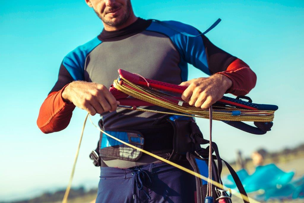 Surfer in wetsuit with kite equipment