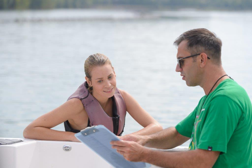 Instructor preparing young lady to water ski for first time