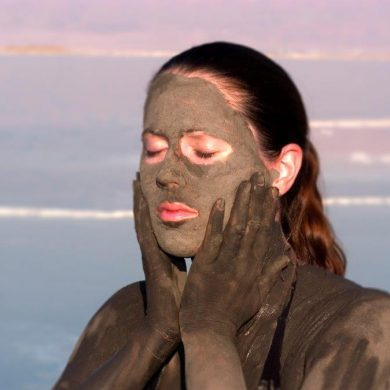 Young lady taking a mud bath at the Dead Sea